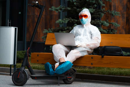 Young Attractive Freelancer Wearing Anti COVID Protecting Suit Working On Laptop Sitting at Bench Near Modern Electric Kick Scooter.