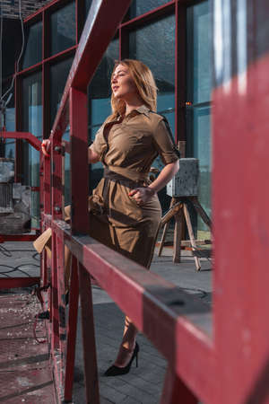 Beautiful Blonde Woman In Stylish Dress At Construction Site Near Construction Cradle. Attractive Worker, Developer Archivio Fotografico