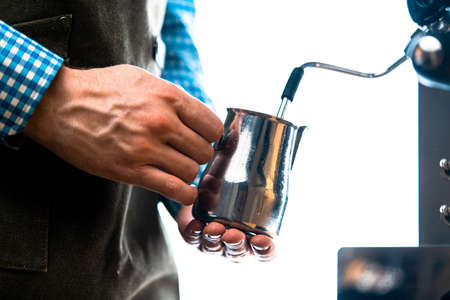 Professional Barista Warming Milk In Metal Jug With Steam Of Coffee Machine. Cappucino Or Latte Coffee Preparation At Home.