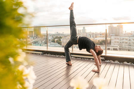 Athletic Man Practicing Yoga in Business Center With Beautiful View on a City From Skyscraper. BusinessMan. Peaceful and Calming Sunset