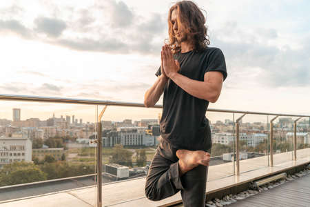Man Looking For Harmony And Balance, Practicing Yoga At Skyscraper Roof On Sunset Background. Enjoying . Concept Of Healthy Lifestyle