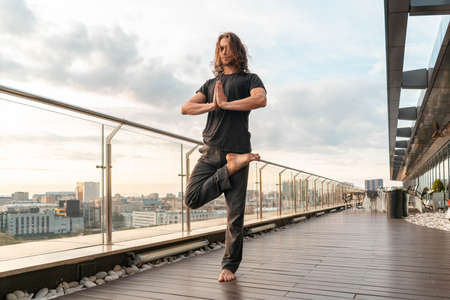 Man Practicing Yoga At Skyscraper Roof On Sunset Background. Enjoying Balance and Harmony. Concept Of Healthy Lifestyle