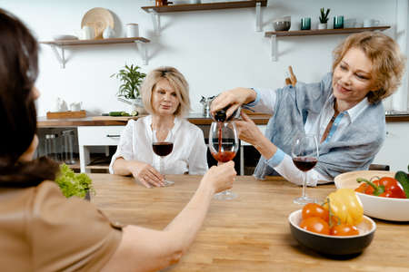 Senior Ladies Drinking Wine And Talking About News In Their Lives. Concept Of Active Lifestyle At Middle Age. Living Full Life. Natural Ageing Archivio Fotografico