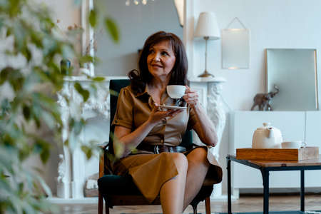 Beautiful Senior Woman Drinking Tea At Living Room and Smiling. Happy Active Life at Any Age. Ageism. Age Shaming Archivio Fotografico