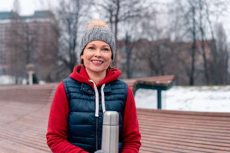 Beautiful Mature Woman Hot Holding  flask In Park After Active Fitness Training With Friends. Active And Cheerful Lifestyle Of Middle Aged People