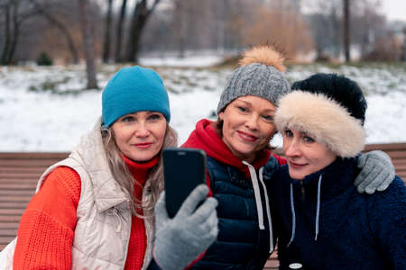 Mature Women Smiling and Making Selfie In Park After Active Outdoors Training. Middle Aged Friends Spending Time Together