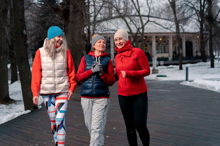 Senior Women Friends Strolling And Talking After Outdoors Training In Park. Active Lifestyle And Friendship at Middle Age. Active And Vibrant Memebers Of Society Archivio Fotografico