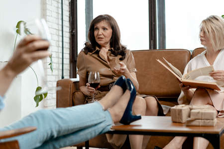 Senior Women Spending Time Together At Drawing Room. Blonde Woman Reading Book. Her Friend Steetched Legs Above Coffee Table. Brunette Woman Drinking Red Wine