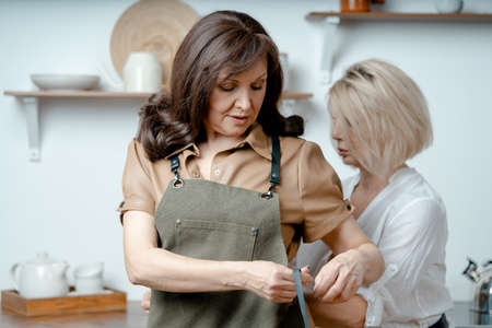 Woman Tying Apron At Her Brunette Attractive Woman At Minimalistic Kitchen. Friendship and Togetherness At Any Age. Natural and Beautifyl Ageing