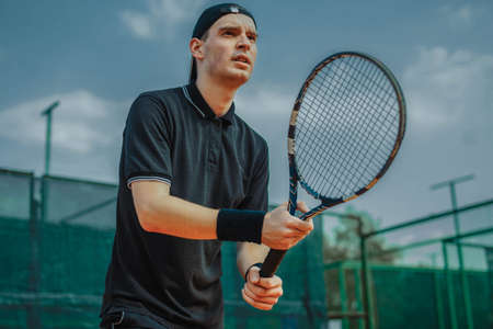 Close up of Man Holding Racket In Both Hands To Straighten Strike While Waiting For Ball Serving At Tennis Court