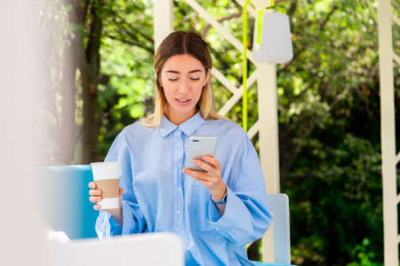 Beautiful Woman Drinking Coffee From Recyclable Cardboard Takeaway Cup at Street Cafe And Chatting At Messenger At Mobile Phone