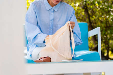 Close Up of Woman Putting Mobile Phone In Cotton Biodegradable Blank White Bag. Eco Friendly Goods. Copy Space. Empty Space