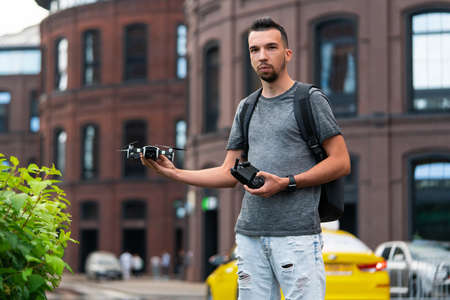 Young Handsome Man With Backpack Launching Drone Quadcopter at Urban Stlilysh Contemporary Cityscape. Modern device Reklamní fotografie
