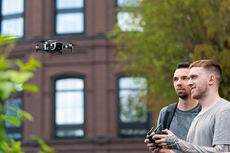 Two Young Handsome Men Launching Drone Quadcopter at Urban Stlilysh Contemporary Cityscape. Modern Device