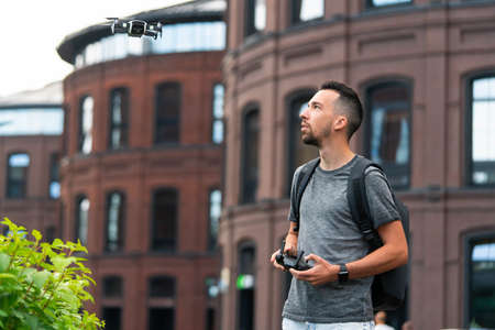 Young Handsome Man Launching Drone Quadcopter and Looking At It. Urban Stlilysh Contemporary Cityscape. Modern device Reklamní fotografie