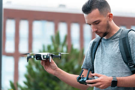 Young Handsome Brunette Man Launching Drone Quadcopter and Looking At Remote Controller Joystick. Urban Stlilysh Contemporary Cityscape. Modern device