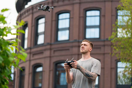 Attractive Tattooed Man Launching Drone Quadcopter and Looking At It. Stylish Red Bricked Building IS on Background. Modern device Reklamní fotografie