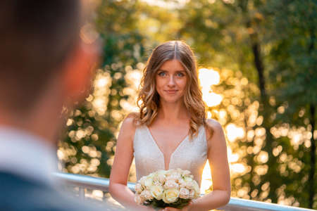 Smiling Happy Bride Holding Wedding Bouquet In Front Of Groom at Wedding Ceremony Outdoors At Park. Groom Is On Foreground And Blurred. Bride is On Background And on Focus