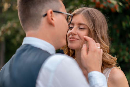 Close up Of Bride Face And Groom Hand Touching Her Face With Tender. Wife Looking AT Husband With Love and Adoration. Wedding Ceremony At Park