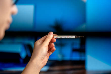 Woman Checking Body Temperature Using Mercury Thermometer In Blue Modern Interior. Health Research Responsibility For Health