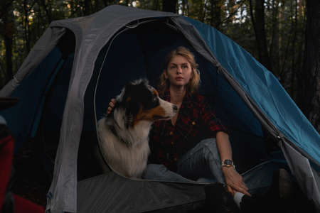 Woman and Aussie Dog Sitting In Tent In Dark Autumnal Forest. Travelling At Native Coutry, Vacation With Closed Borders