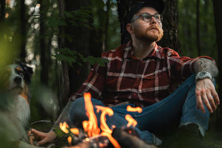 Bearded Hipster Man Near Bonfire In Dark Autumnal Forest an Looking At Sitting Sun. Travelling At Native Coutry, Vacation With Closed Borders
