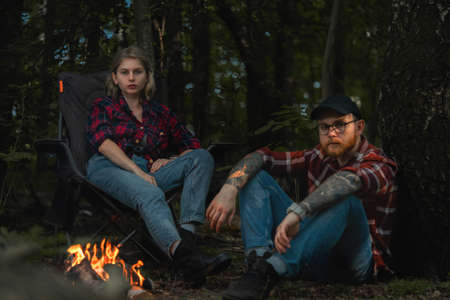 Beautiful Backpacker Woman And Man Having Rest Near Bonfire After Hiking In Forest. Contains chrominance noise, luminance noise, sharpening noise, or film grain