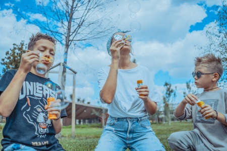Young Stylish Mum and Two Sons Blowing Bubbles In The Park and Having Fun.