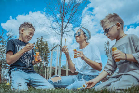 Young Stylish Modern Mum and Two Sons Blowing Bubbles In The Park and Having Fun.