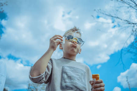 Little Blond Boy Blowing Out Bubbles At Park. Concept of Happy Family And Childhood