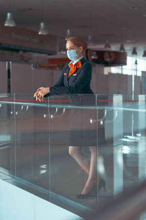 Flight Attendant With Protecting Mask At Empty Airport. Covid-19 Outbreak Travel Restrictions. Flight Cancellation 版權商用圖片