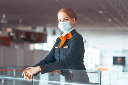 Close up Of Beautiful Red Head Flight Attendant With Protecting Mask At Empty Airport Without Passengers and Light. Travelling During Epidema