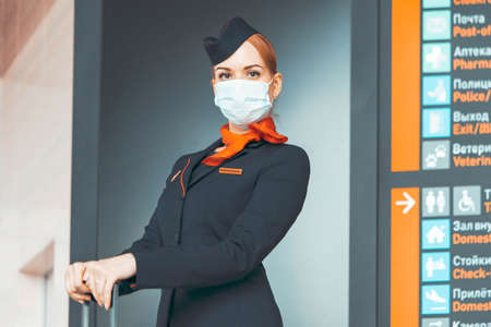 Attractive Flight Attendant With Protecting Mask Staying Near Arrival Board. Empty Airport Without Passengers. Covid-19 Outbreak Travel Restrictions. Flight Cancellation