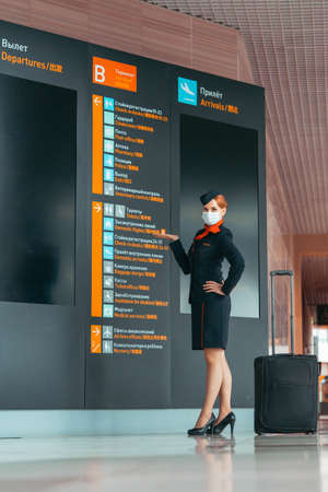 Flight Attendant Wearing Protecting Mask and Stay Near Departure And Arrival Board. Empty Airport Without Passengers. Coronavirus Pandemia. Covid-19 Outbreak Travel Restrictions. Flight Cancellation