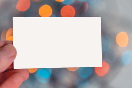 Blank White Business Card Hold By Man Hand on Christmas Garland Background. Festive Mood And Vibes 版權商用圖片