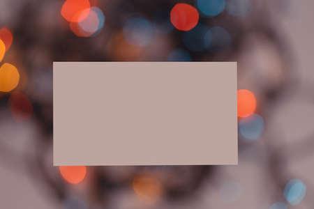 Blank white business card on the blurred garland light Reklamní fotografie