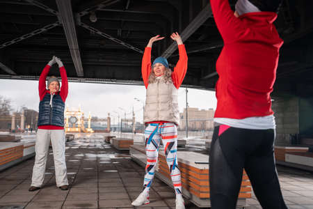 Healthy Middle Aged Women Warming Up And Stretching Arms in Urban 版權商用圖片