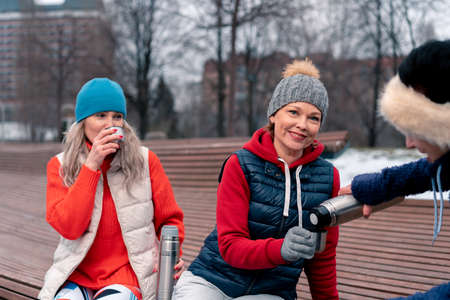 Mature Woman Pouring Hot Tea From Thermos To Her Friend After Active Fitness Training In Park. Active Lifestyle Of Middle Aged.