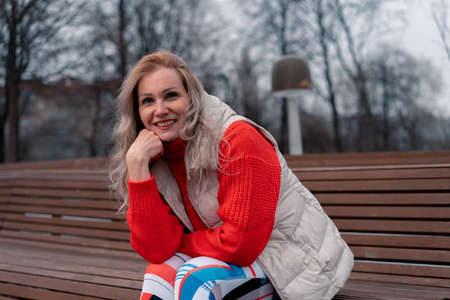 Mature Blonde Woman Smiling And Sitting On Bench In Park After Exercising. Active Lifestyle Of Senior Aged People 版權商用圖片
