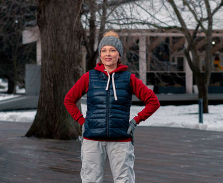 Beautiful Mature Woman IWarming Up At Park. Active and Healthy Lifestyle at Middle Age.