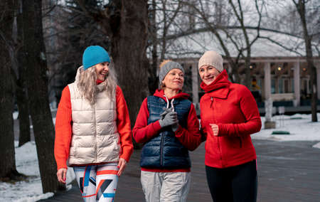 Mature Women Friends Walking In Park After Morning Run And Talking About News 版權商用圖片