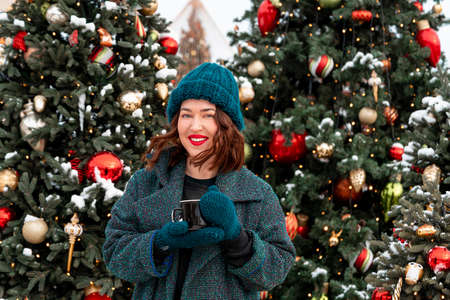 Beautiful Brunette Woman Holding Cup Of Hot Cacao Or Tea With Christmas Tree on Background. 2021 版權商用圖片