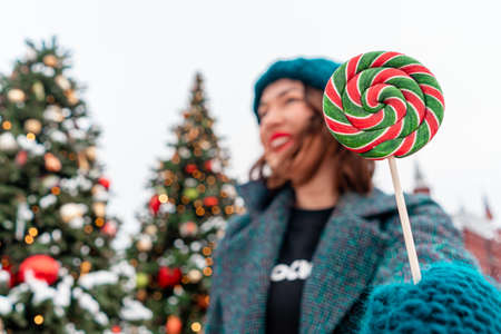 Cheerful Brunette Woman Holding Lollipop At Christmas Fair. Girl And Pines With New Year Decoration Are On Background And Blurred