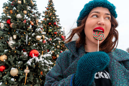 Happy Brunette Woman Licking Lollipop Near New Year Trees With. Celebrating New Year Eve of 2021 and Spending Holidays With Joy