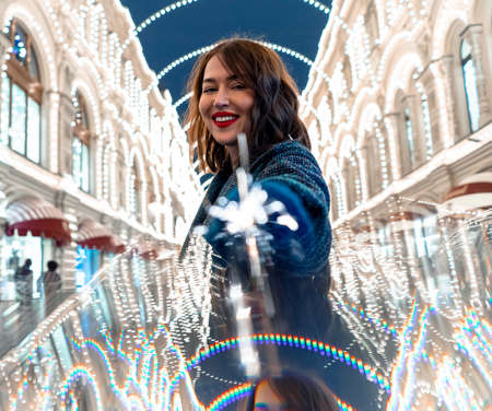 Beautiful Brunette Woman Holding Sparkler And Smiling Near Decorated With Christmas Lights Building. New Year And Christmas Celebration 2021 版權商用圖片