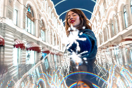 Cheerful Young Woman Holding Sparkler And Smiling Near Decorated With Christmas Lights Building. Celebrating New Year Eve 2021 With Bengal Light