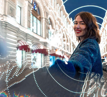 Attractive Woman Holding Bengal Light And Smiling Near Decorated With Garlands Building. New Year And Christmas Celebration. 2021 版權商用圖片