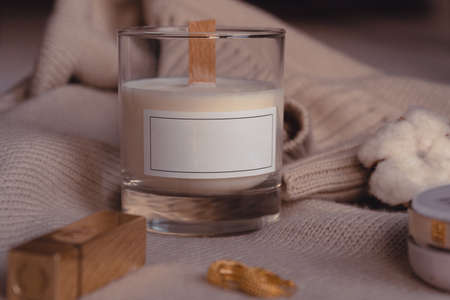 Composition Of Scented Candle, Cozy Stylish Sweater. Cotton Flower, Lipstick, Earrings And Powder. Candle In Glass With Blank White Label