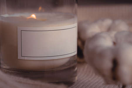 Close Up Of Burnng Scented Aroma Candle In Glass With Blank White Label Near Cotton Flower On Cozy Stylish Sweater 版權商用圖片