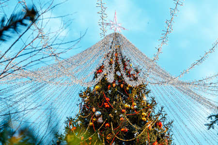 Abundantly Decorated Christmas Tree At Sunny Bright Winter Day Before New Year. Christmas European Fair